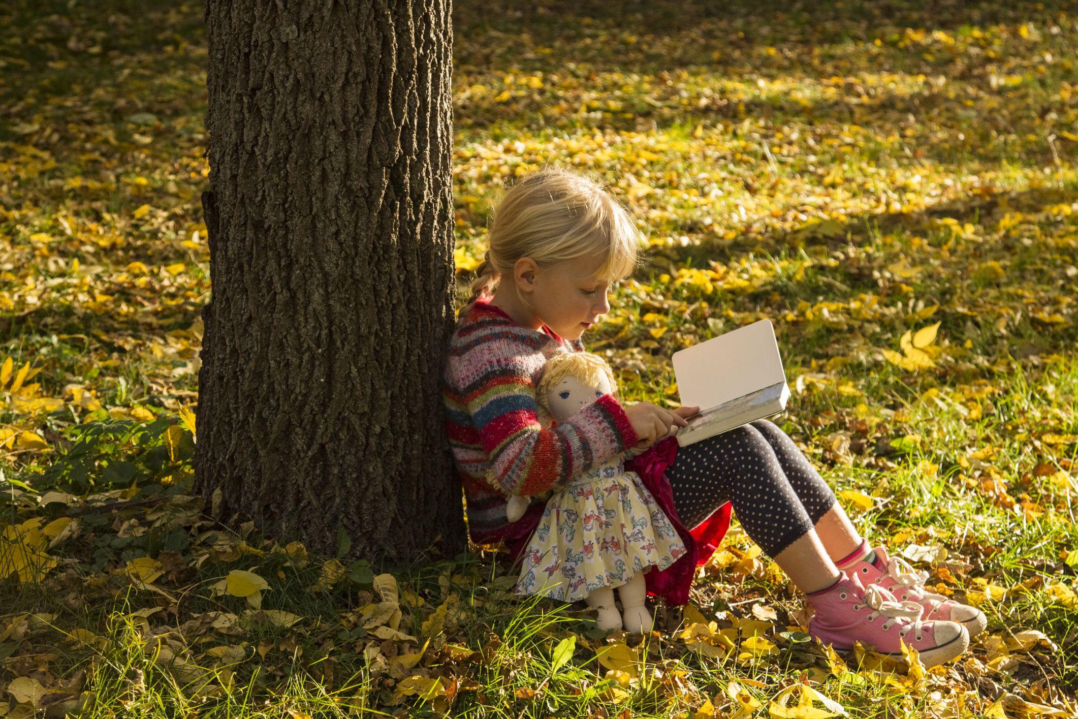 Ein Mädchen, das ein Buch mit ihrer Puppe unter einem Baum liest.