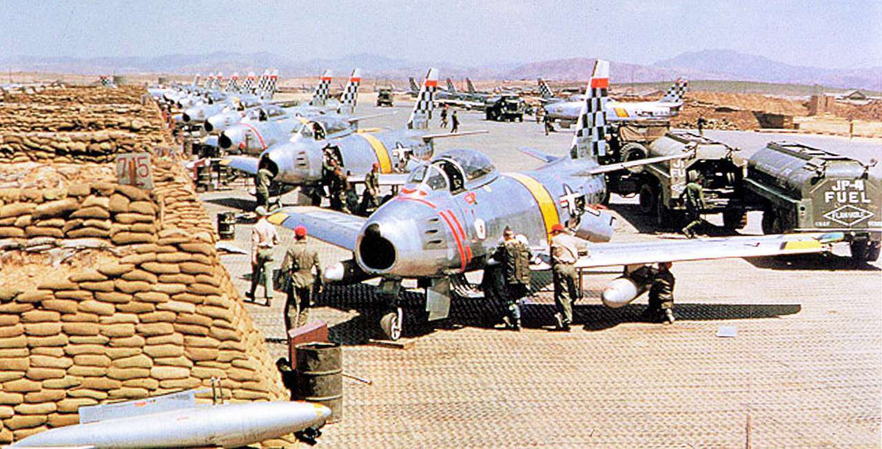 F-86 Sabres lined up on a runway near a wall of sandbags.