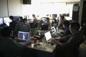 Hackers working a hackathon at laptops in dark office