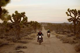 two people riding motorcycles through the desert