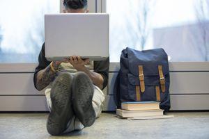 College student using laptop on floor