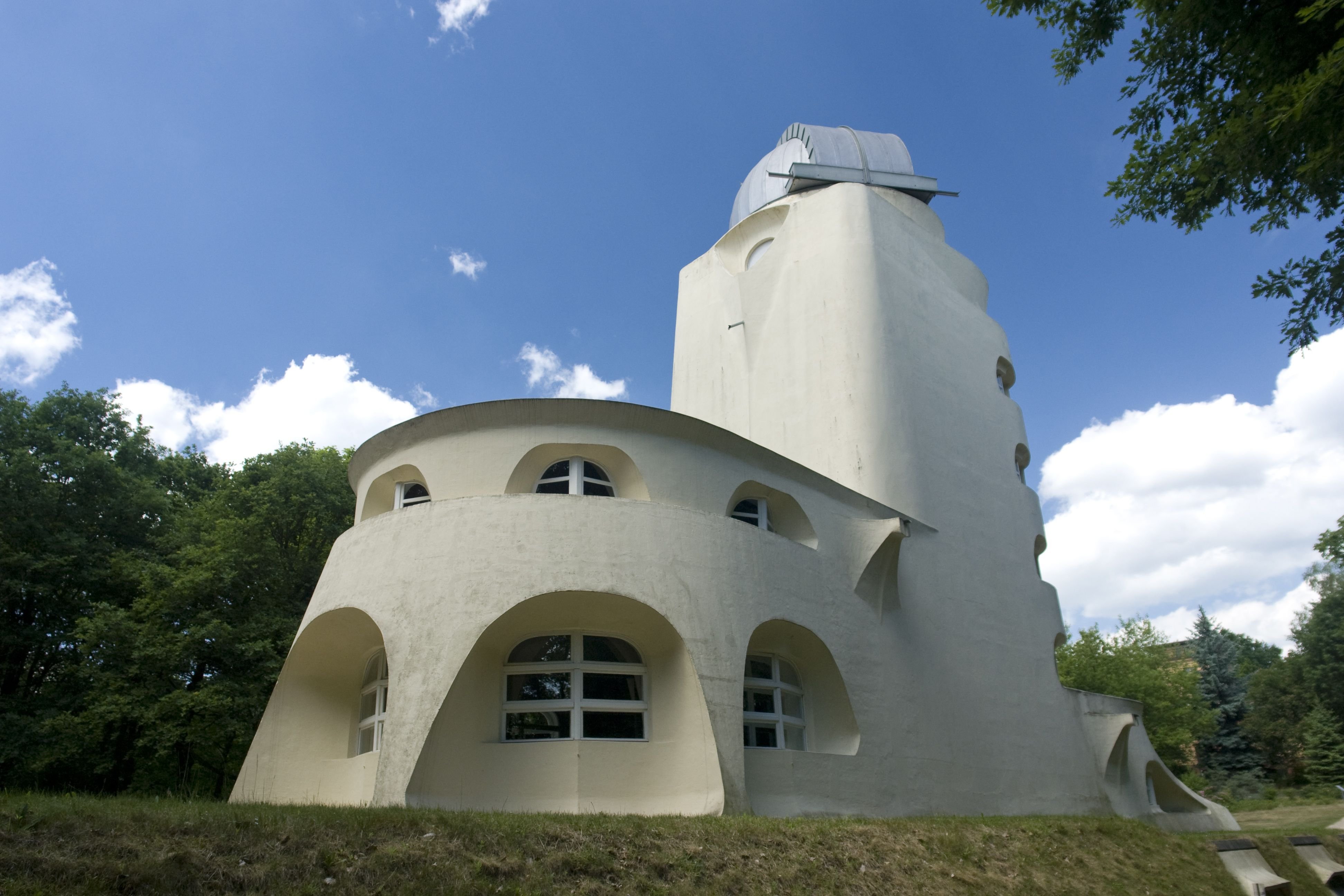 white, curvy 1 1/2 stoy building with arched curvy windows and attached tower