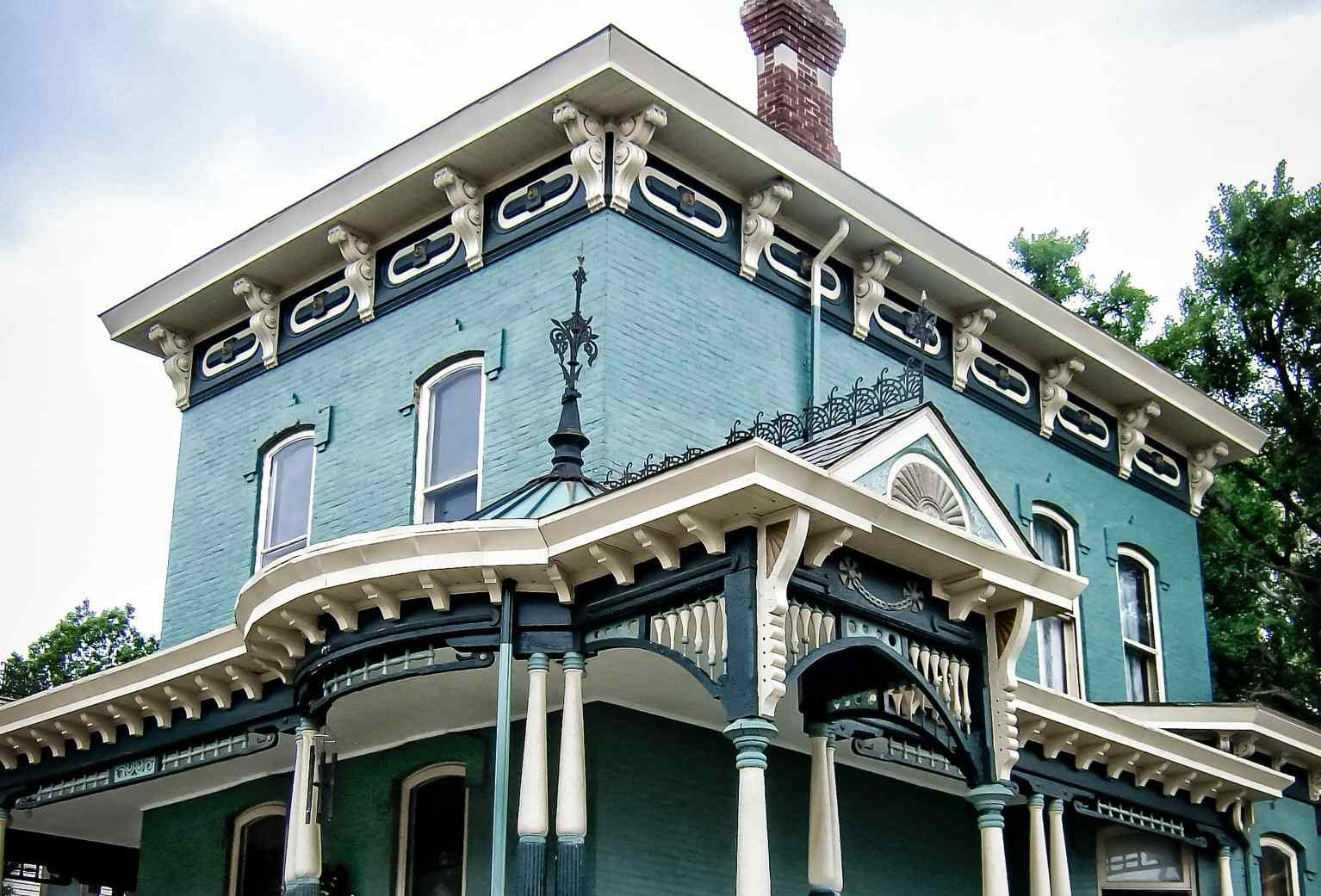 Corbels on ornate Victorian house with flat roof that overhangs and porch roof that overhangs, both having corbels in the eaves
