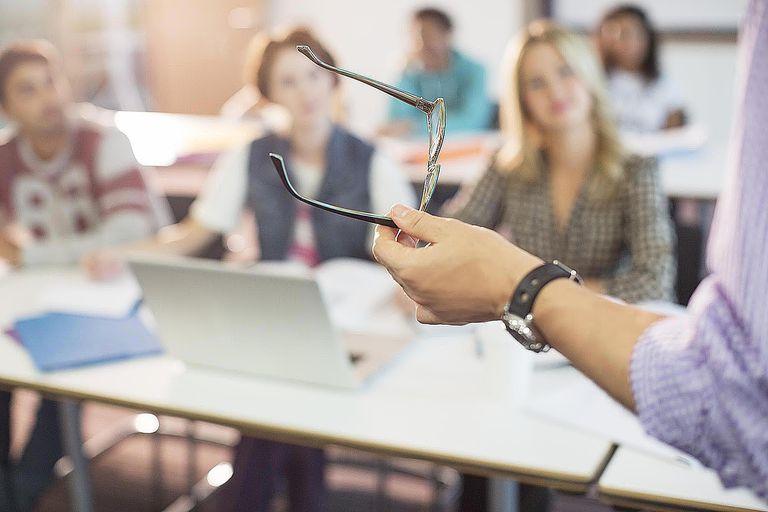 Professor gesturing with eyeglasses in cla...