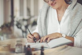 Woman writing in a calendar