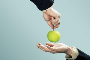 Someone handing someone an apple