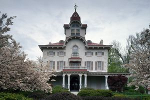 Two and a half story Italianate mansion with arched central tower protruding from a slightly sloped roof