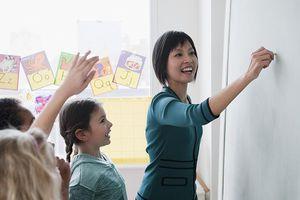 Teacher writing on blackboard with students