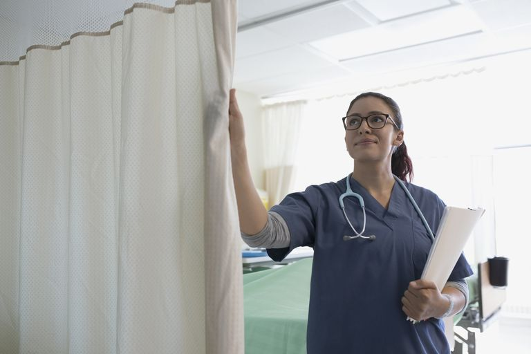 Female nurse closing hospital curtain