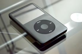 Black and white photo of an iPod on a glass table.