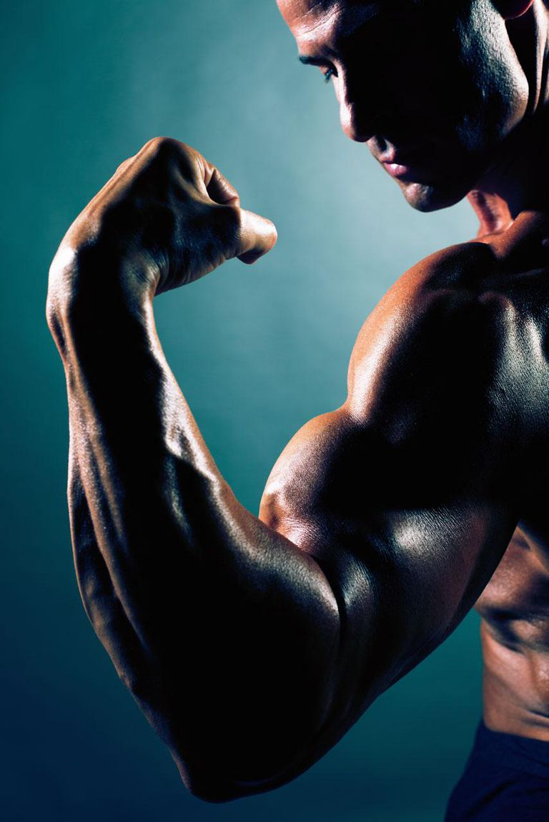 Muscular caucasian man flexing his bicep, close-up, studio shot