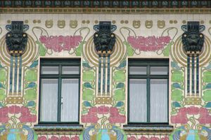 detail close up of facade, two windows surrounded by patterns of colorful tiles and symmetrical sculptings