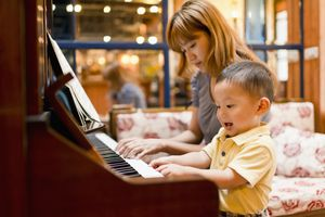 Mother and child play piano