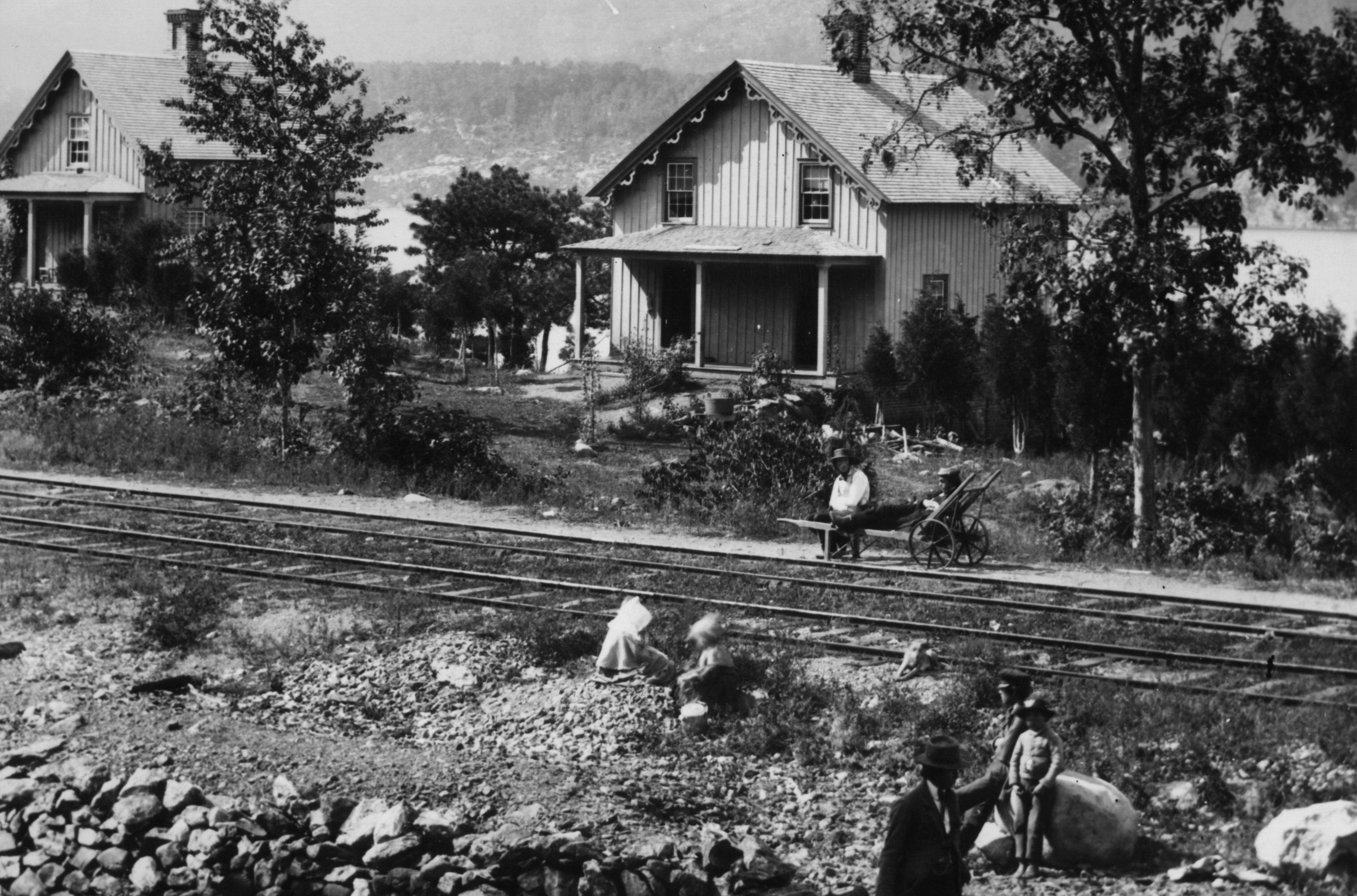 historic black and white photo of houses by railroad tracks