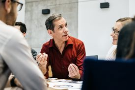 man speaking with other business people