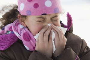 girl blowing her nose outdoors in winter
