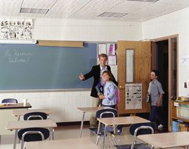 Teacher welcoming students (9-12) to classroom on first day of school