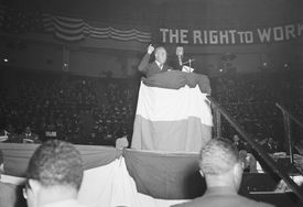 Black and white photo of a man speaking at a podium, with a