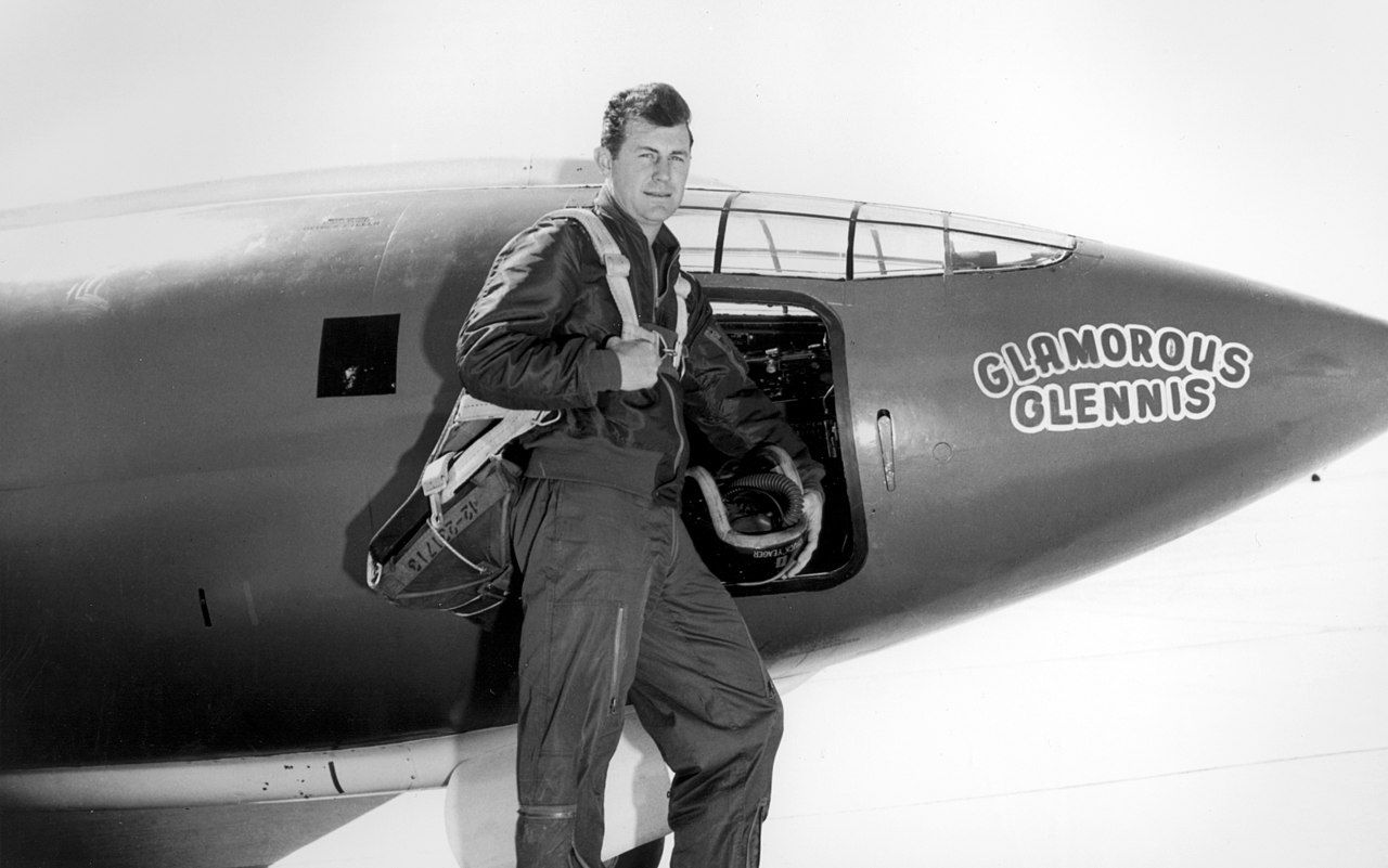 Chuck Yeager in flight suit standing in front of Bell X-1.