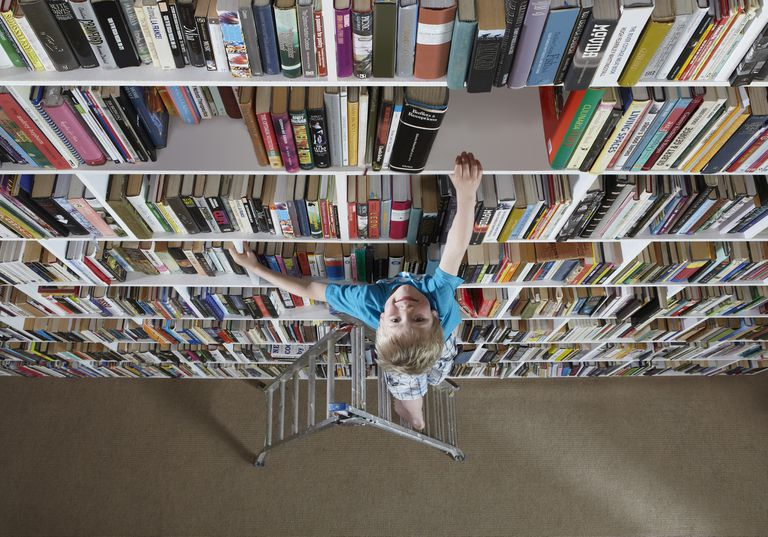 Boy using stepladder on bookshelves