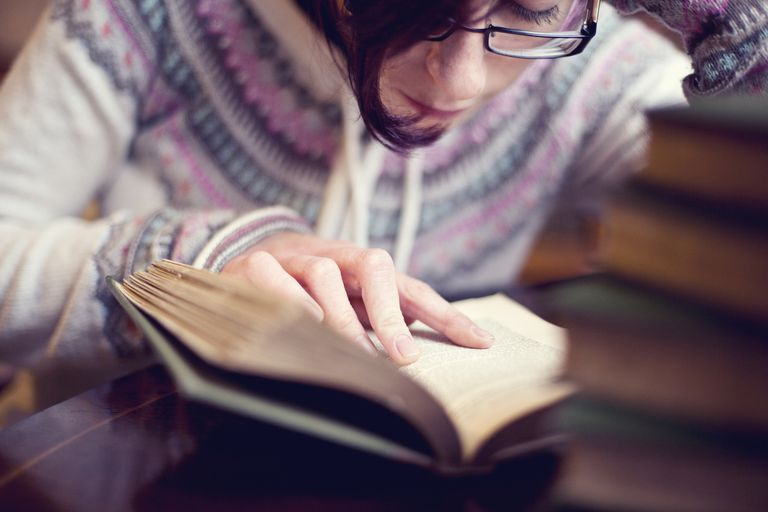 Young woman with glasses reading a book