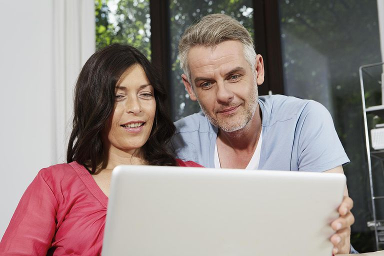 Germany, Berlin, Mature couple using laptop, smiling