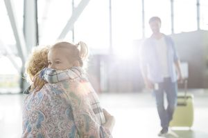 Mother and daughter hugging at the airport with father in background