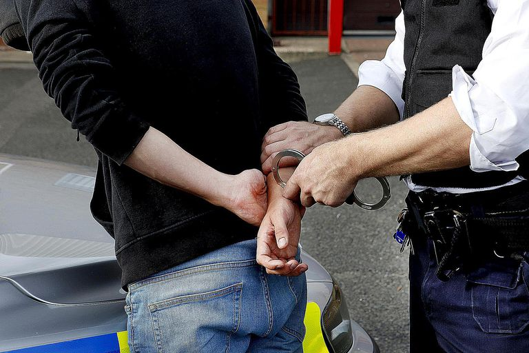 A police officer handcuffs a suspect. Find out how sociologists approach the study of deviance and crime.