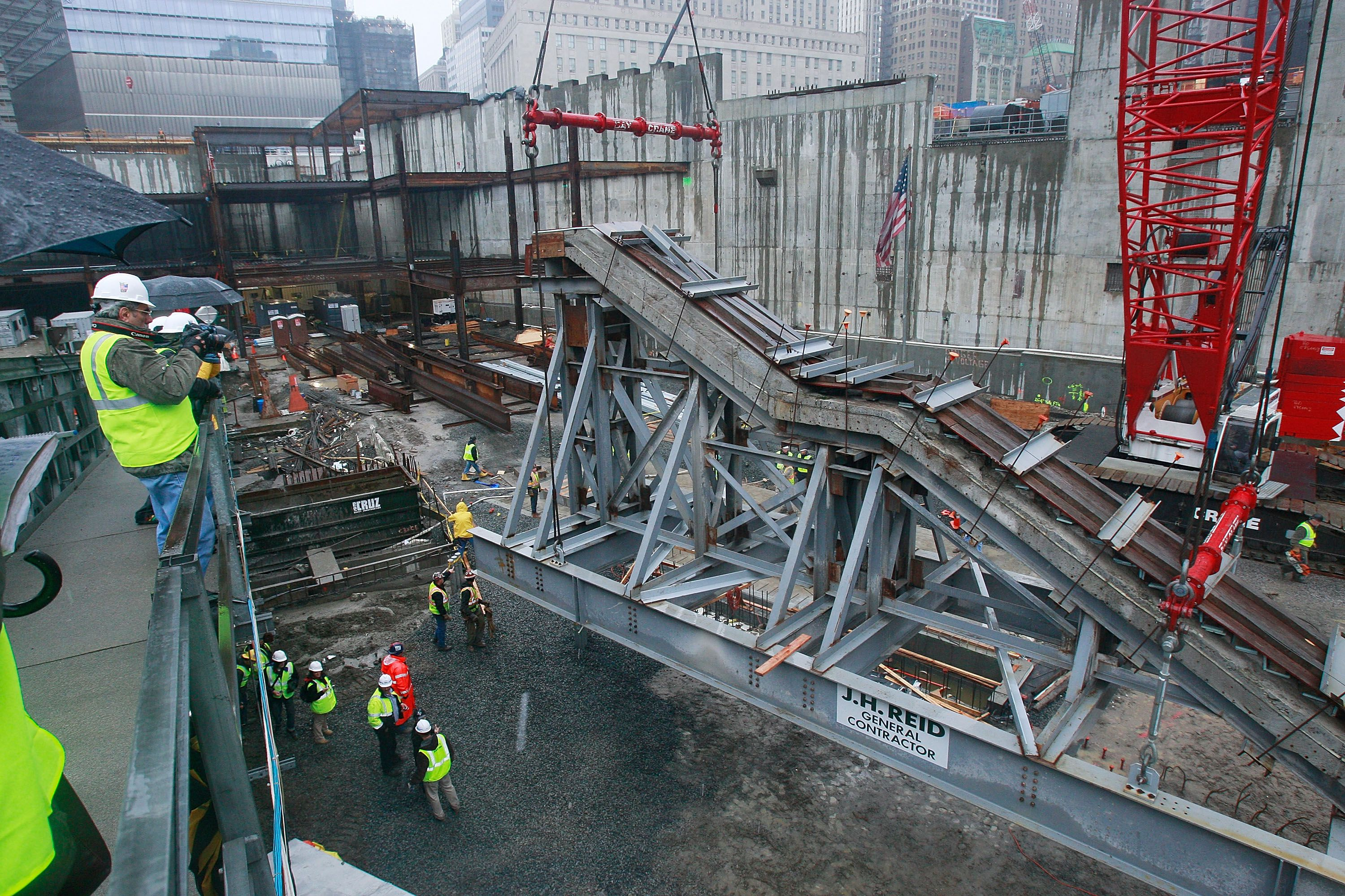 sloped metal piece in pit surrounded by construction workers