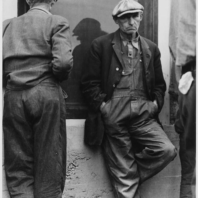 Unemployed men standing in the streets, unable to find jobs during the Great Depression.