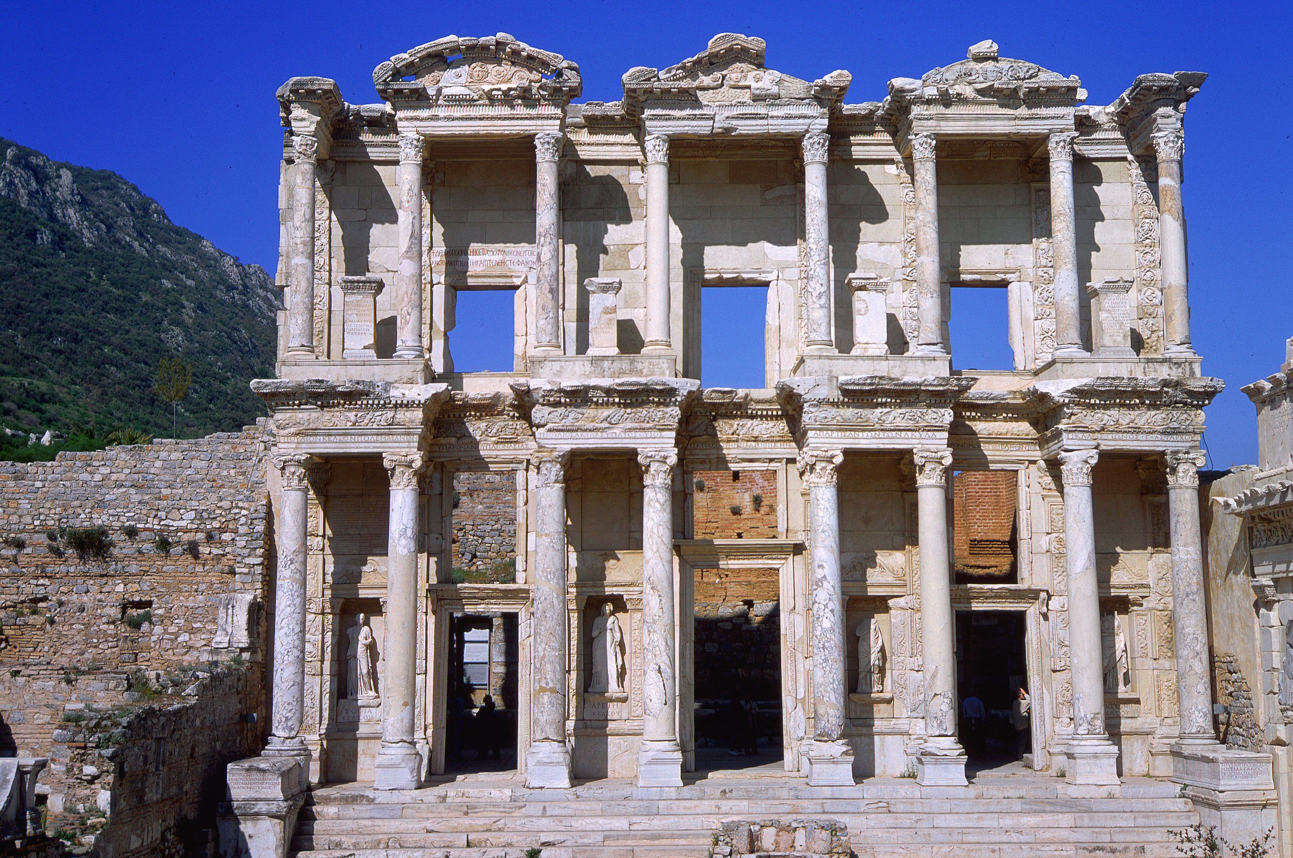 facade of ruined ancient building with columns and pediments, two stories