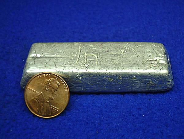 Photograph of the metal indium, with a penny to indicate the size of the sample.