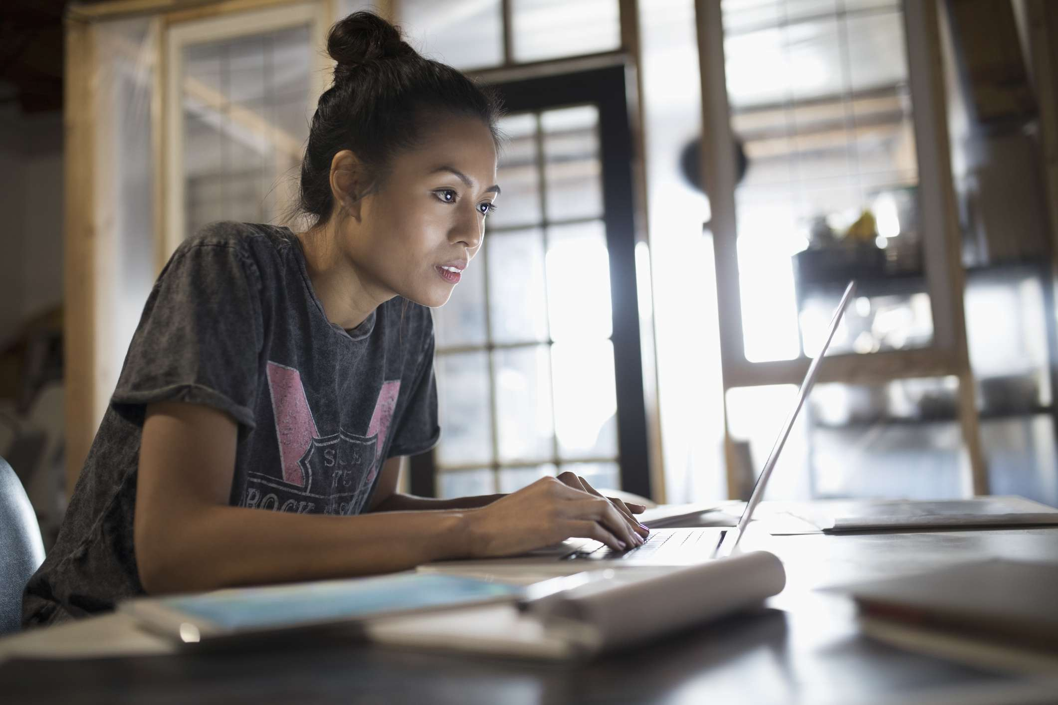 Focused young woman working at laptop in office