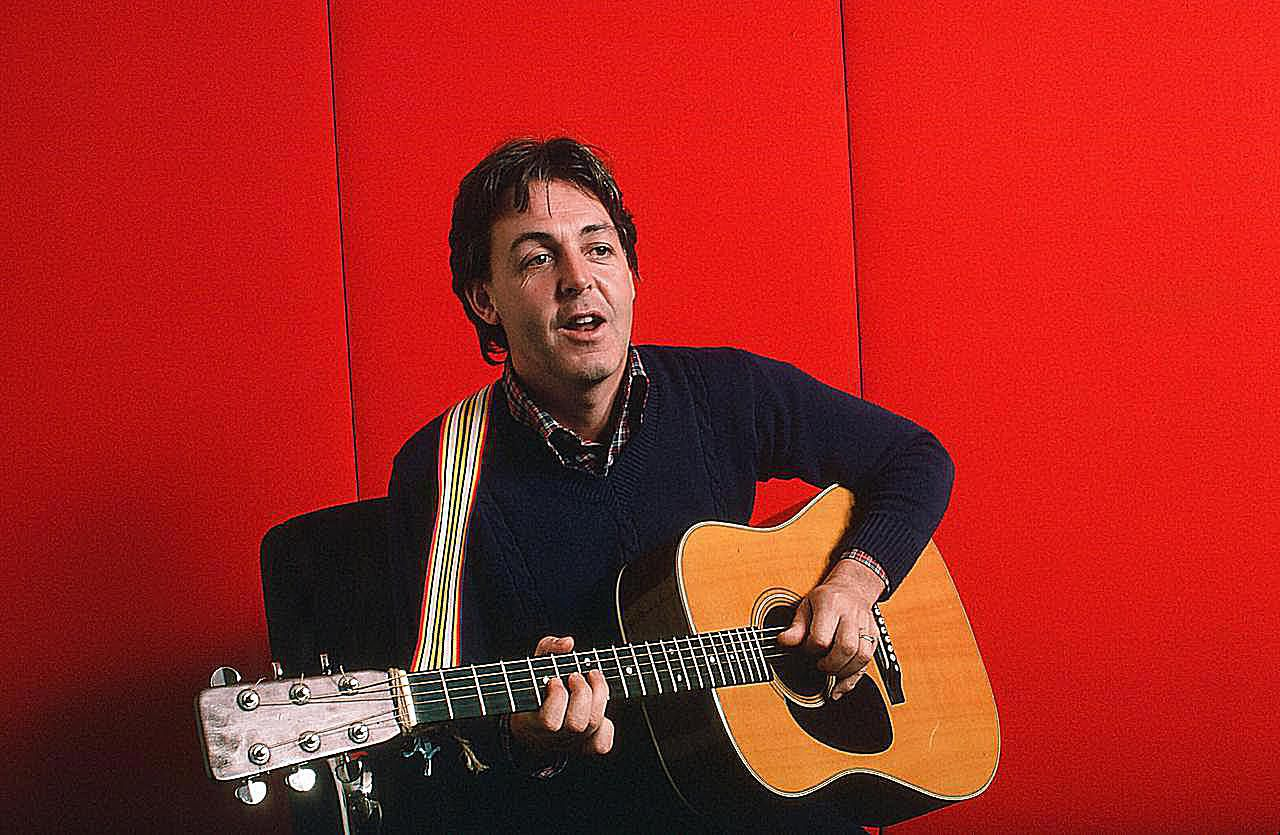 Paul McCartney, ktorý hrá na akustickú gitaru na červenom pozadí, 7. októbra 1984.