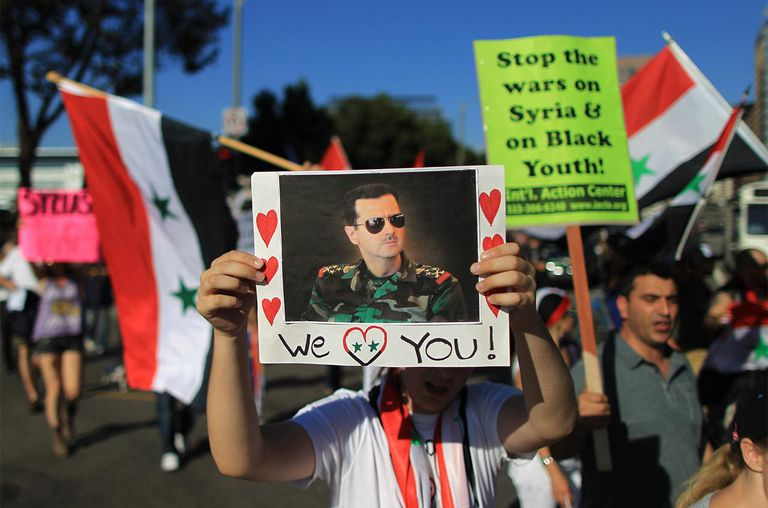 A supporter of Syrian President Bashar Hafez al-Assad expresses love for the president at a rally to urge Congress to vote against a limited military strike against the Syrian military