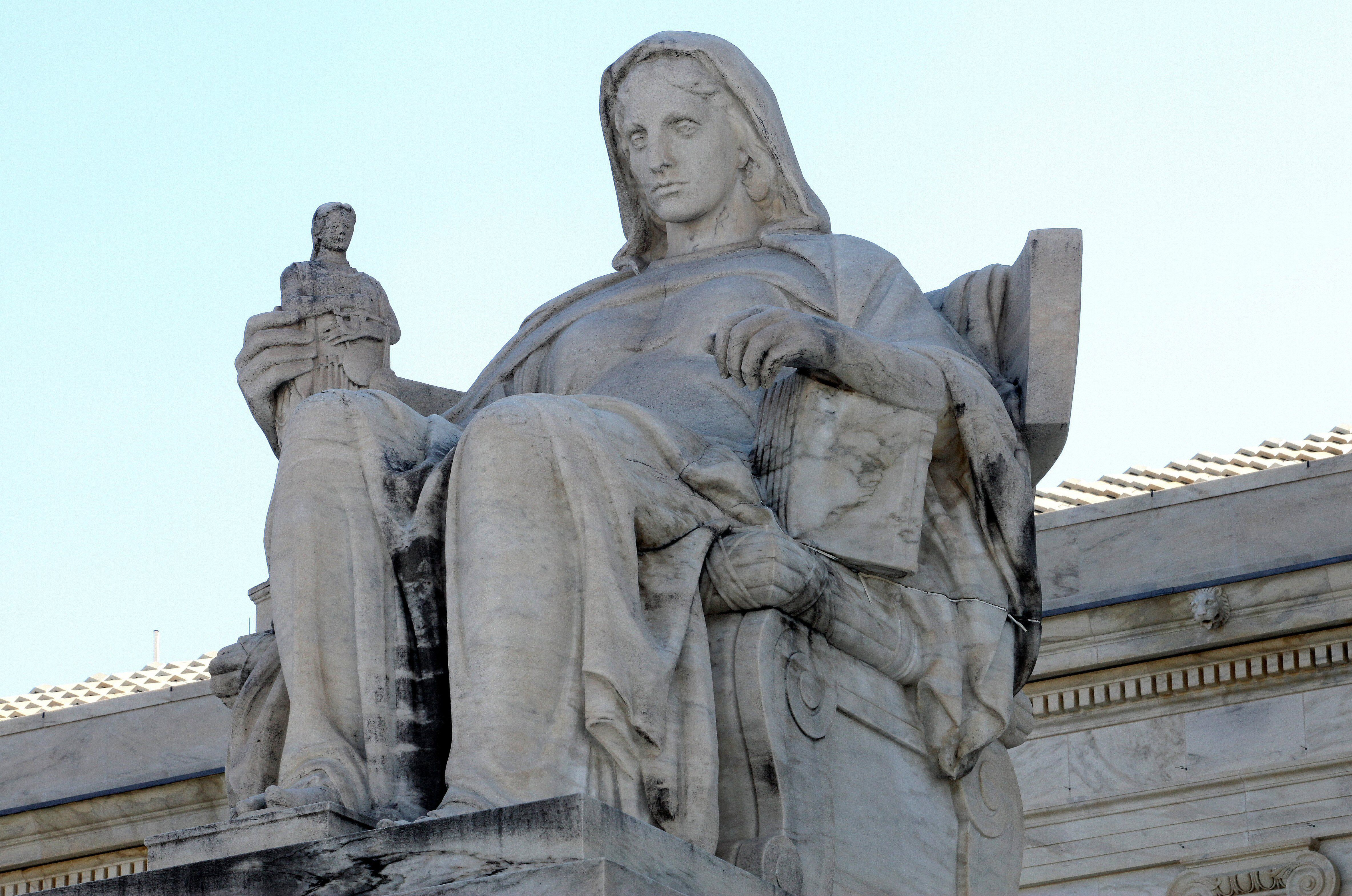 detail of an outdoor sculpture of a large female figure, with her left arm resting on a book of law, is thinking about the smaller female figure in her right hand