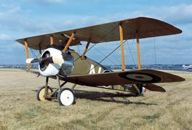 A British Sopwith Camel parked in a grass field on a sunny day.