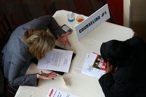 A career adviser assisting a client at a job fair