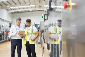 Supervisor and worker using digital tablet in factory