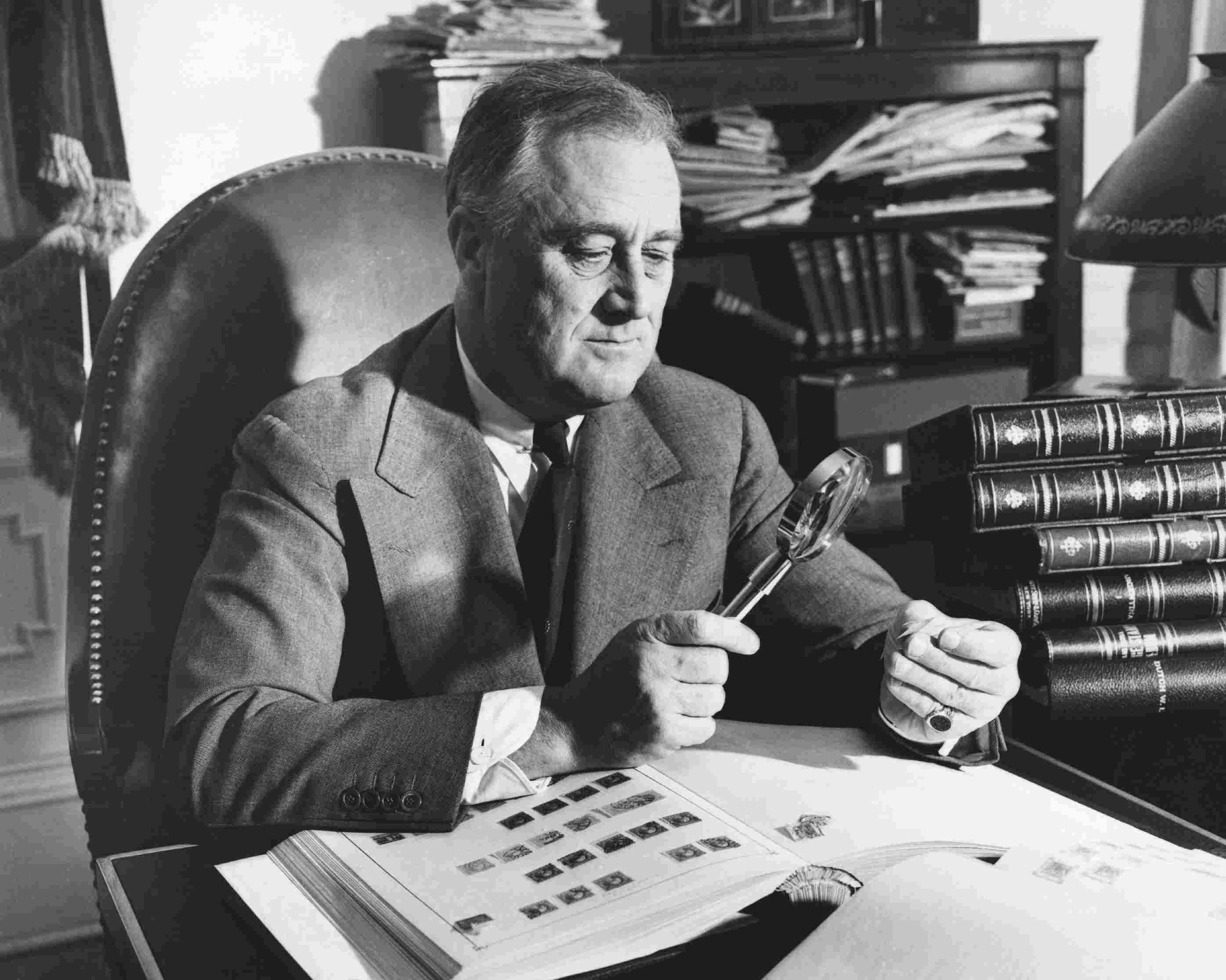 President Franklin Roosevelt looks at a stamp with a magnifying glass