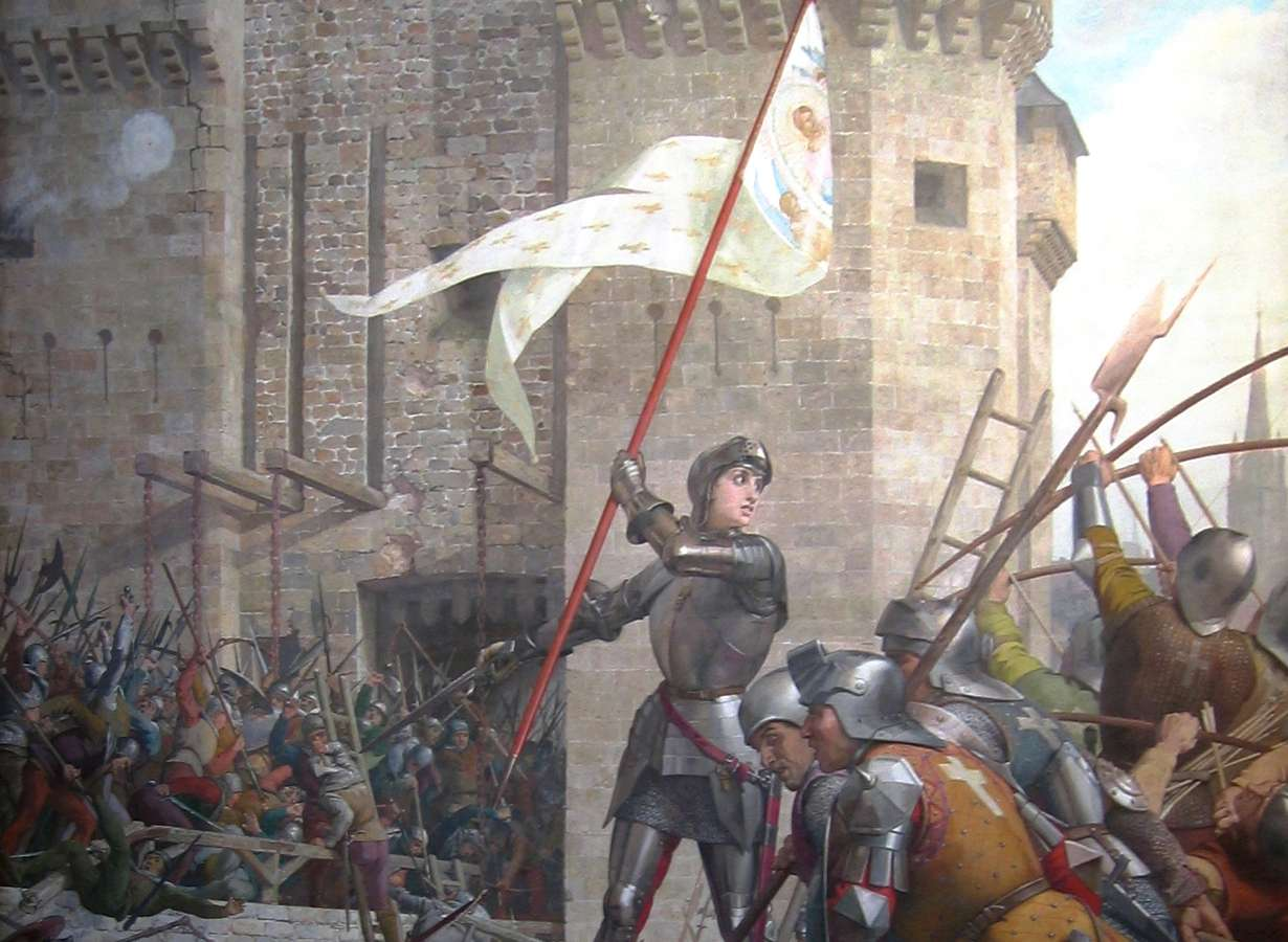 Joan of Arc in armor waving a white and gold flag in front of soldiers.