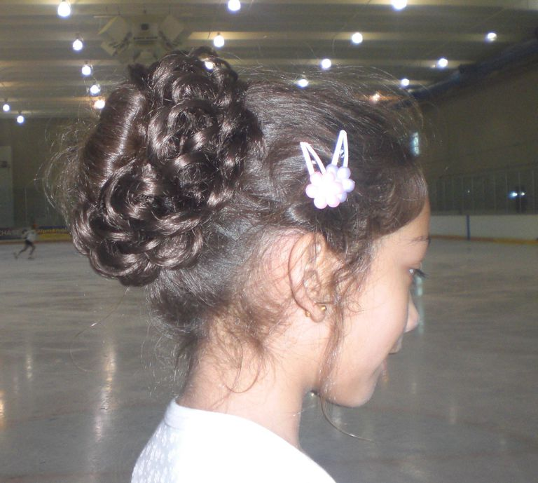 A Skater Wears Her Hair Pulled Back and Up for Figure Skating