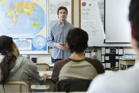 teacher in a classroom in front of a map