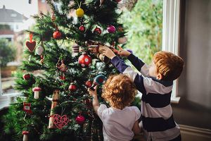 Small children decorate a Christmas tree