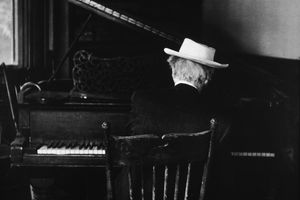 old black and white photo of the back of an old man with a hat sitting in a spindle chair playing the piano