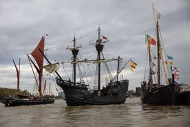 Three boats with flags on a river.