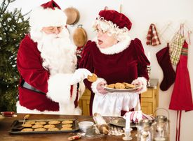 Santa taking a cookie from Mrs. Claus