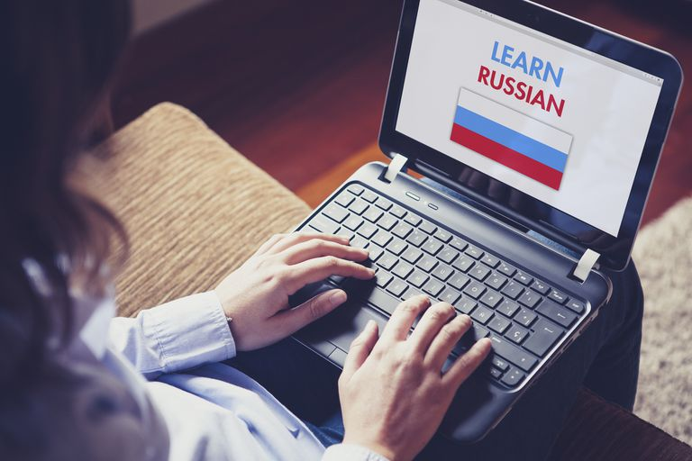 Female learning russian at home with a laptop