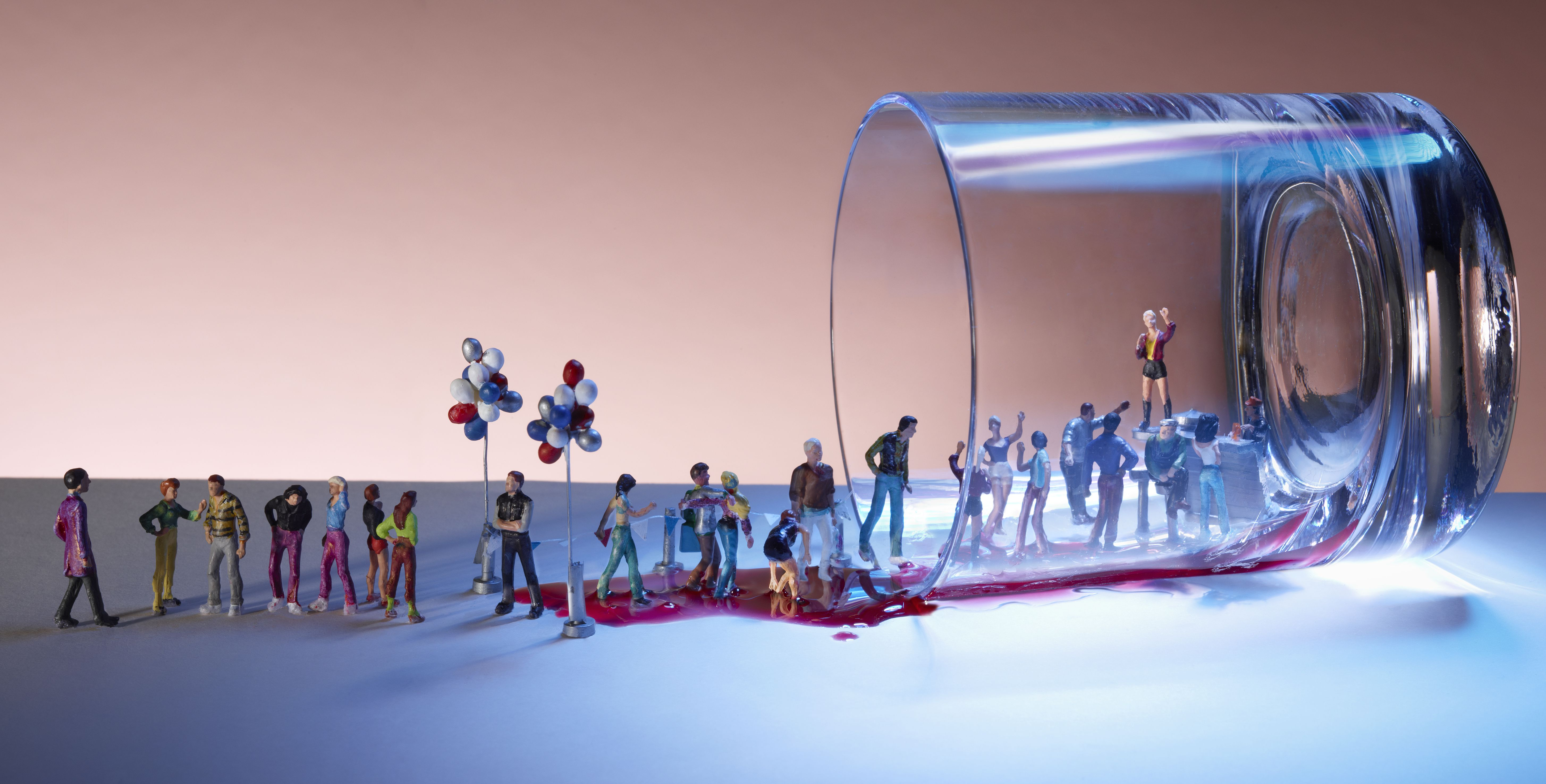 Miniature people queuing at a nightclub happening inside a spilled cocktail glass