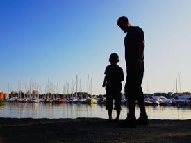 Father and son looking at boats in Stockholm, Sweden.